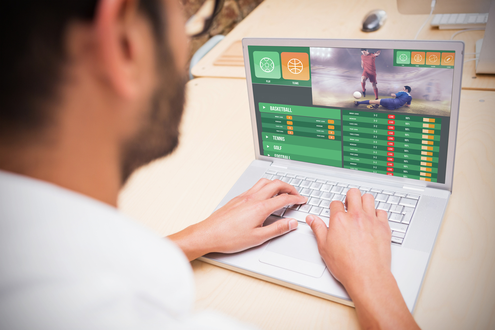 man betting on soccer on laptop