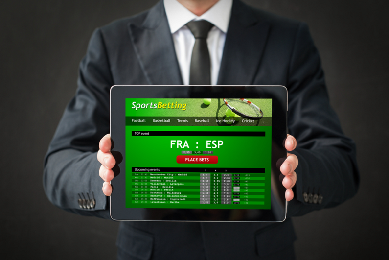 businessman showing sports betting website on tablet