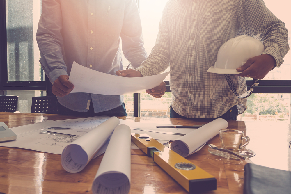 architects at work with plans and level tool on office desk