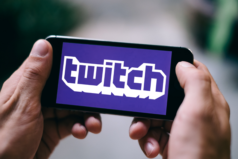 male holding iPhone displaying Twitch logo