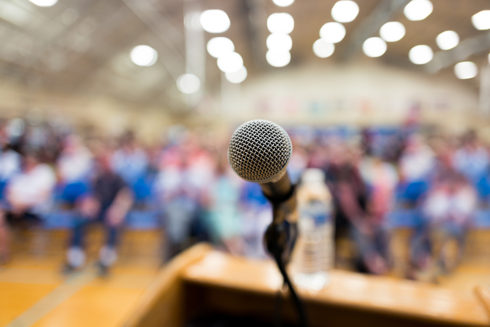 microphone on podium with audience in auditorium