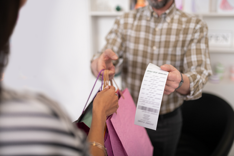 male seller providing a client with bright shopping packages and a receipt