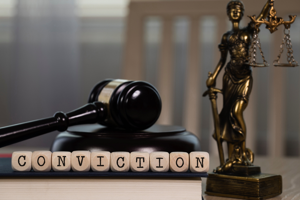 """CONVICTION"" spelled out with dice, with judge's gavel and statue of Themis"