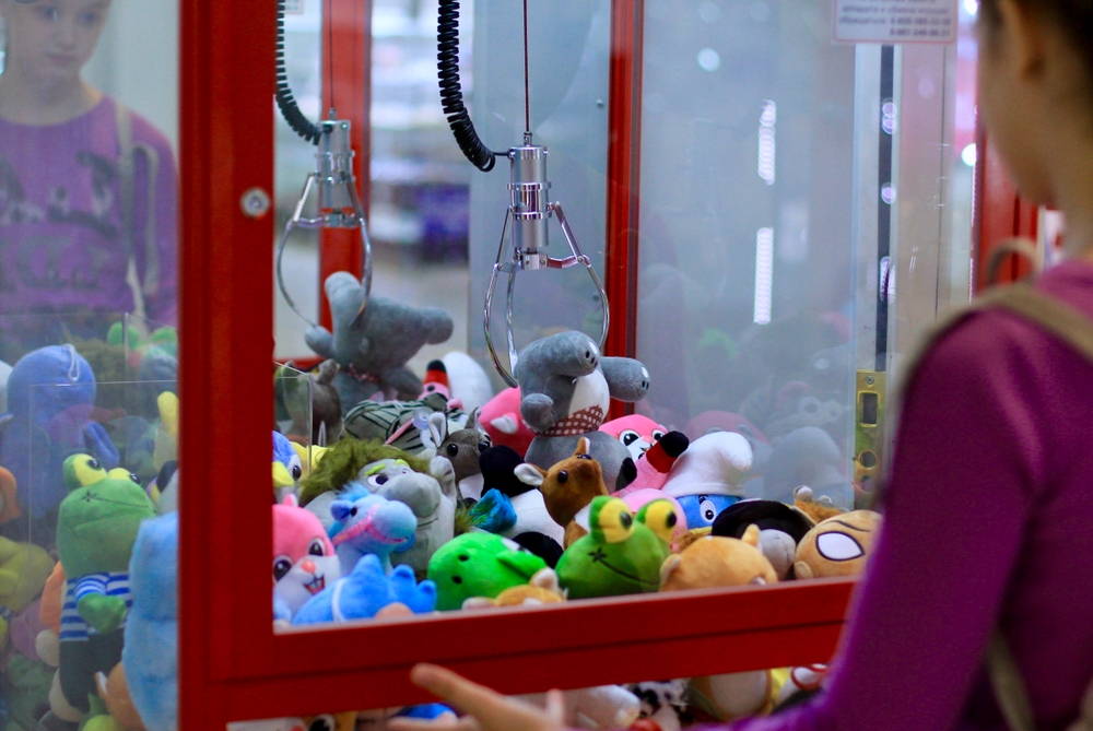 girl playing at claw machine