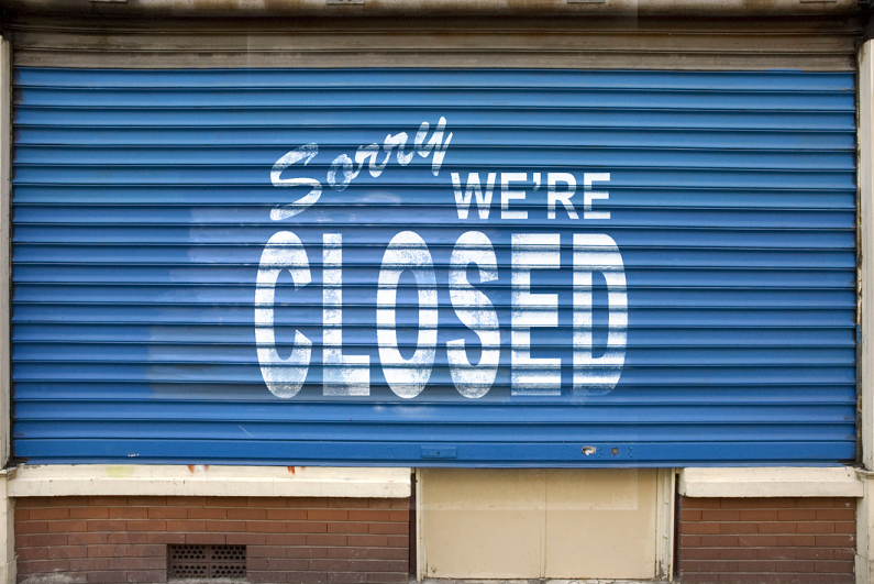 store shutters with 'sorry we are closed' printed
