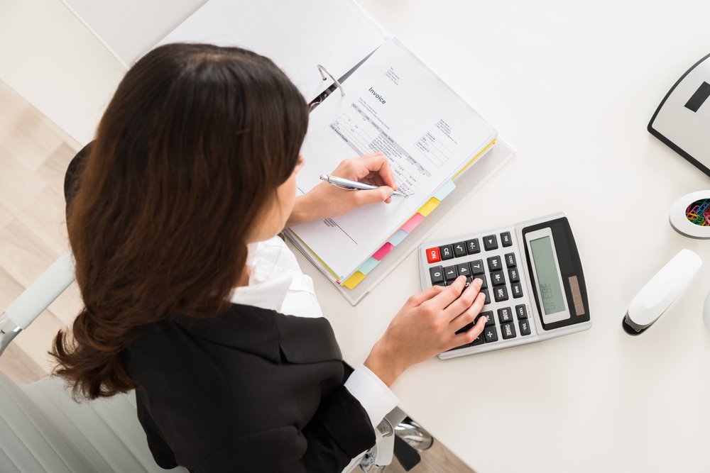 woman working out accounts using a calculator