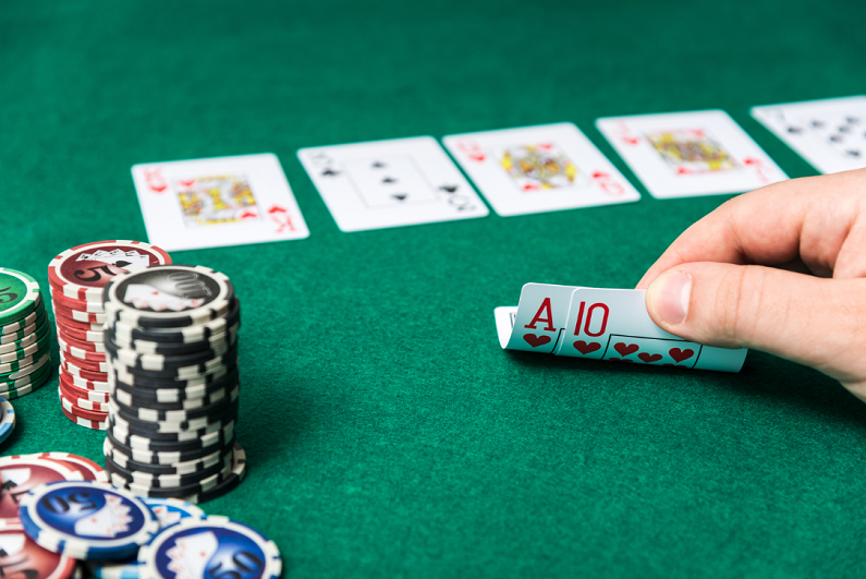 poker player peeking at hole cards at poker table