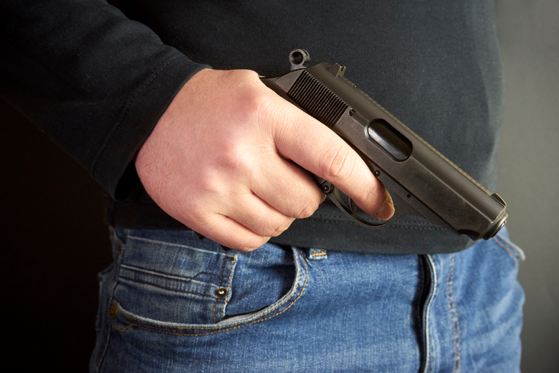 male holding a handgun