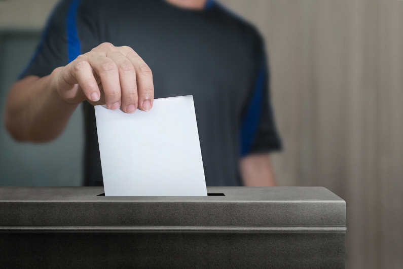 male inserting vote in ballot box