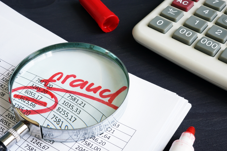 fraud written on paper under a magnifying glass