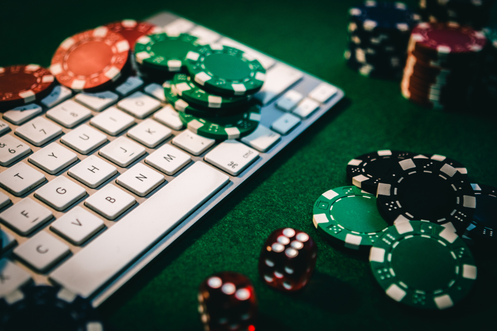poker chips and dice on and around computer keyboard