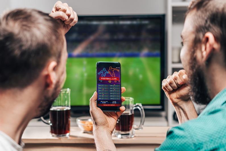 两名男子看足球比赛,庆祝胜利的赌注