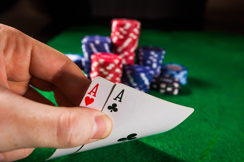 poker chips with two aces on green background