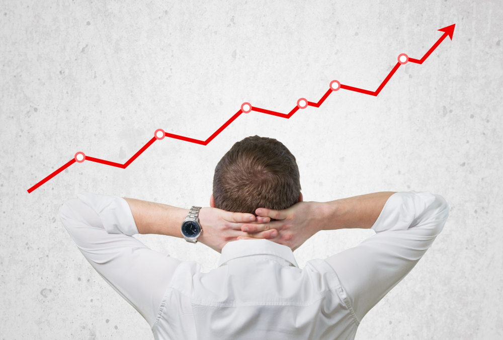 businessman observes rising trend on graph