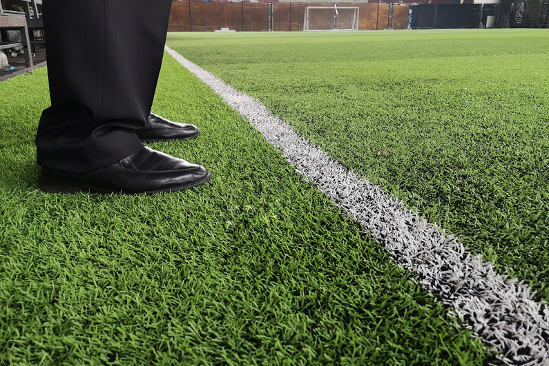 coach standing at side of pitch