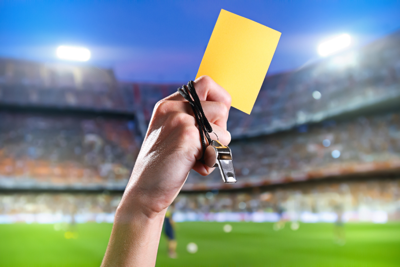 referee with yellow card and whistle