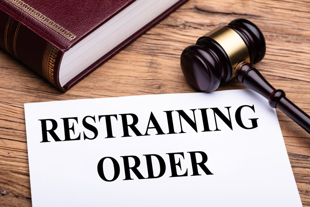 restraining order document, judge's gavel, and a law book