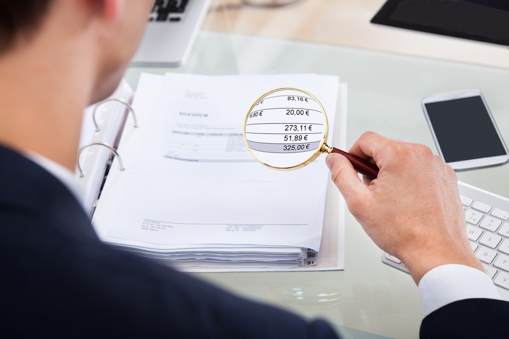 auditor examining invoice with magnifying glass at desk