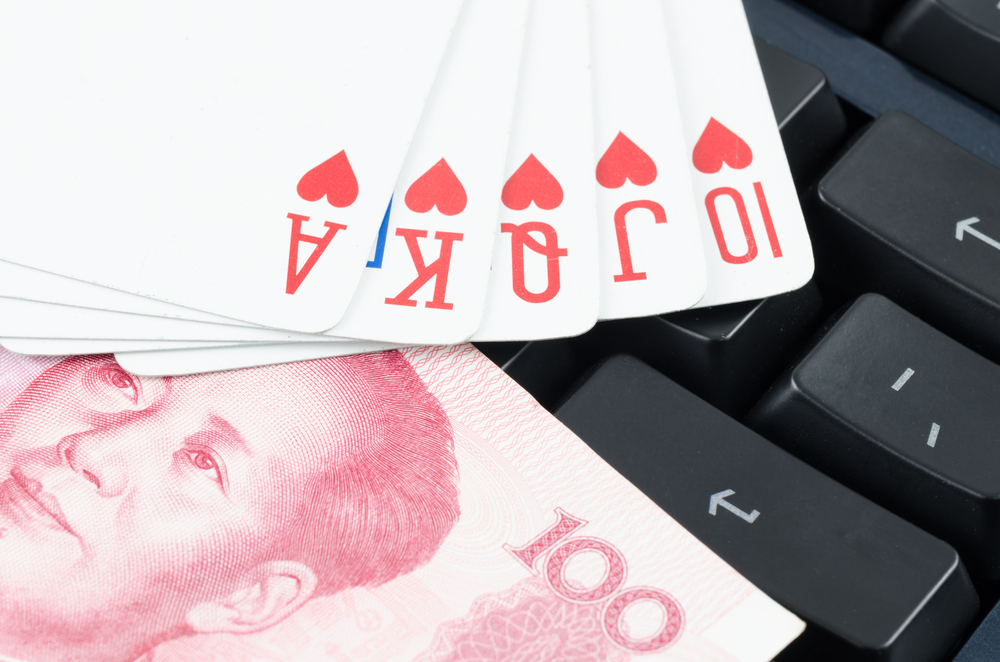 playing cards and Chinese yuan on computer keyboard