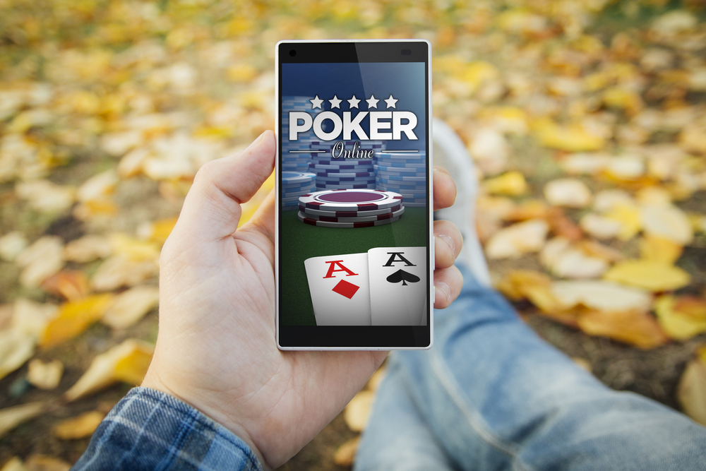 man holding smartphone with mobile poker app outdoors