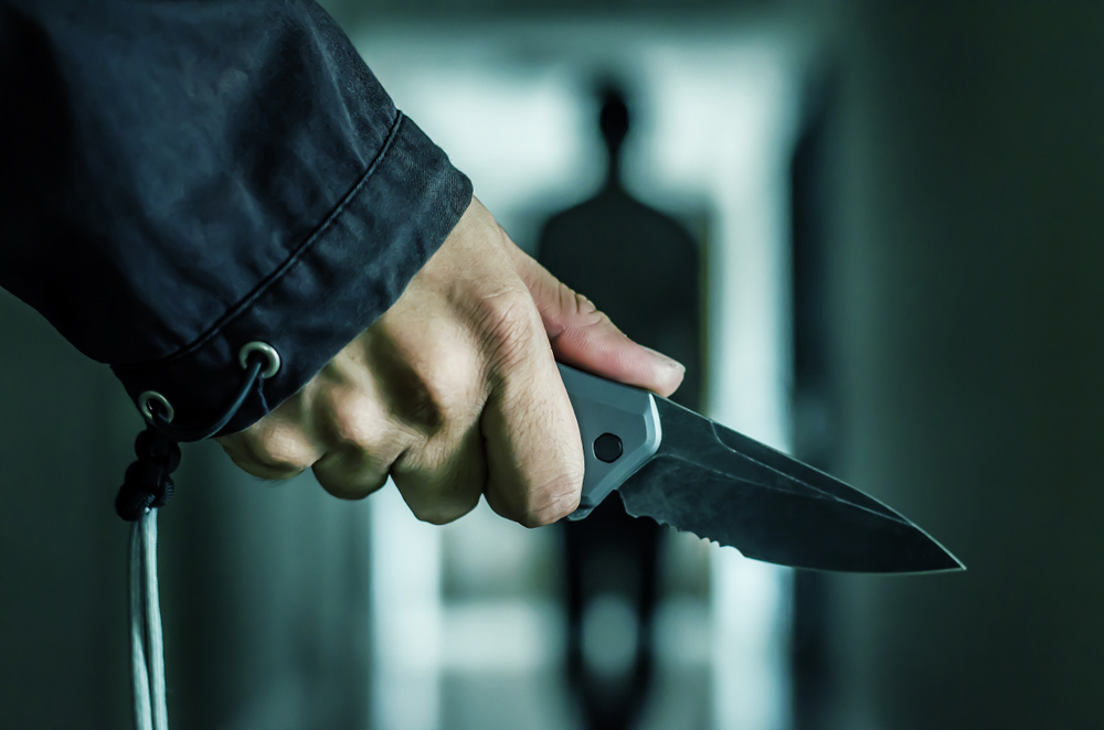 hand pulling knife on an approaching person