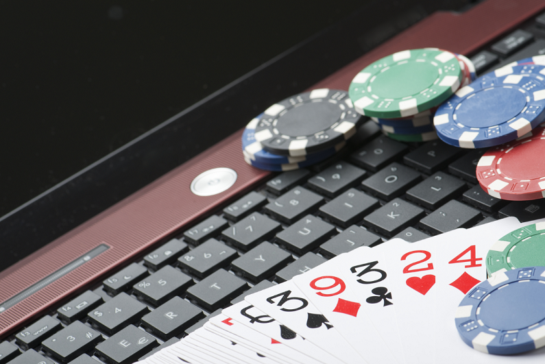 casino chips and cards on laptop
