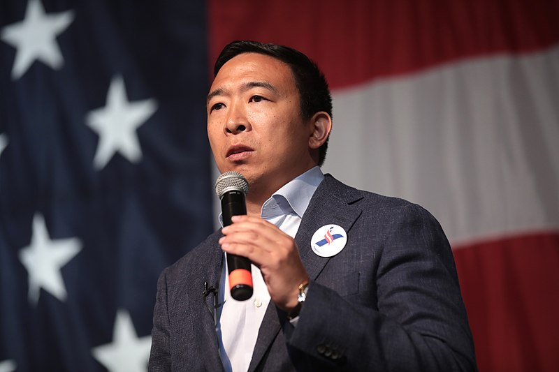 Andrew Yang giving a speech with US flag in the background