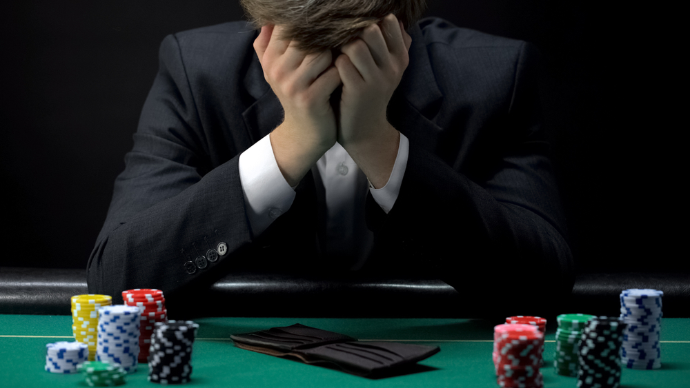 poker player holding head in hands after losing game