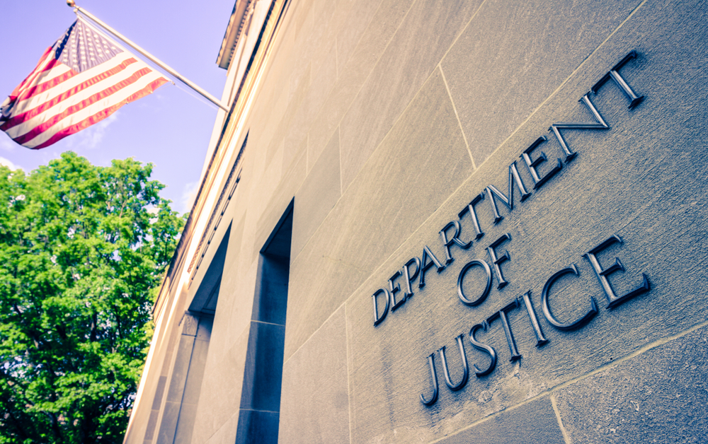 Department of Justice lettering and US flag outside Washington State building