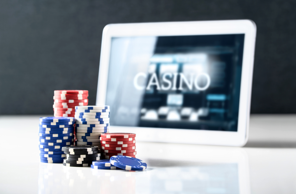 poker chips with ipad showing online casino screen in background
