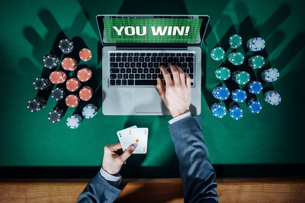 man in suit holds cards as he plays online poker on laptop surrounded by chips