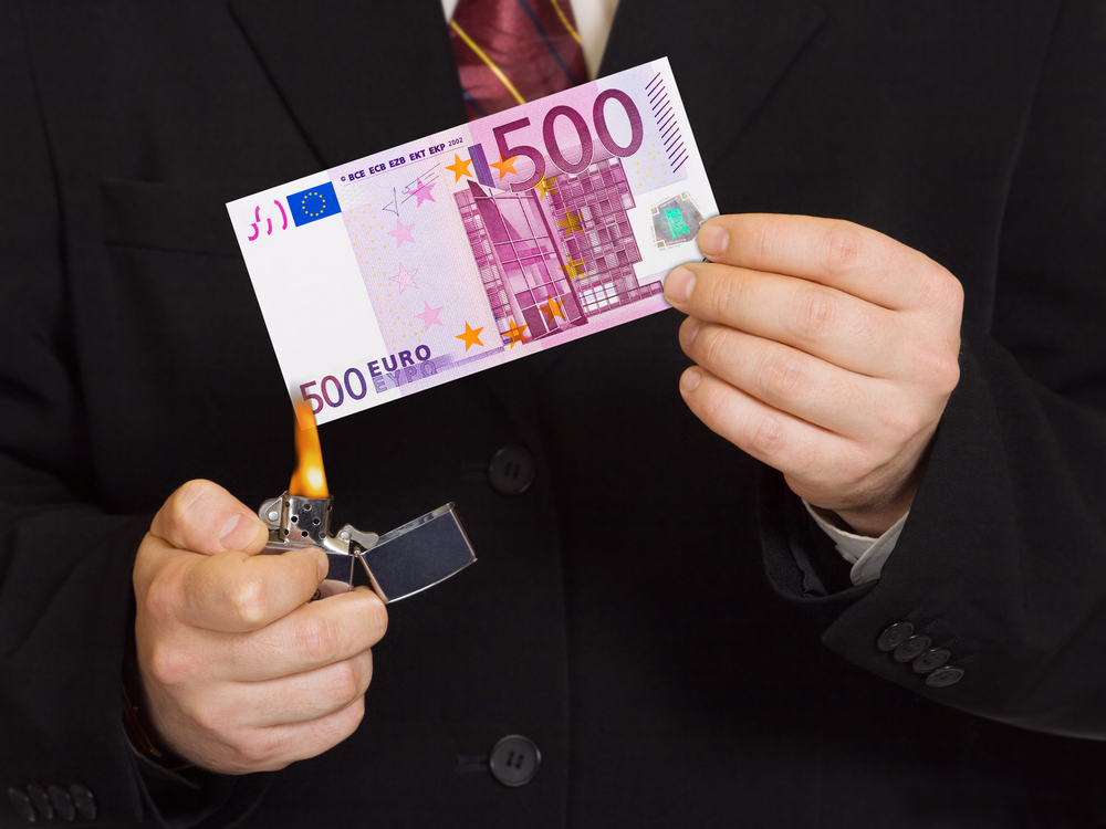 businessman setting fire to 500 euro note