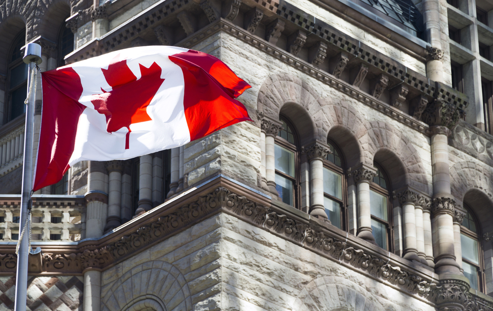 flag of Canada against grey-stone building background