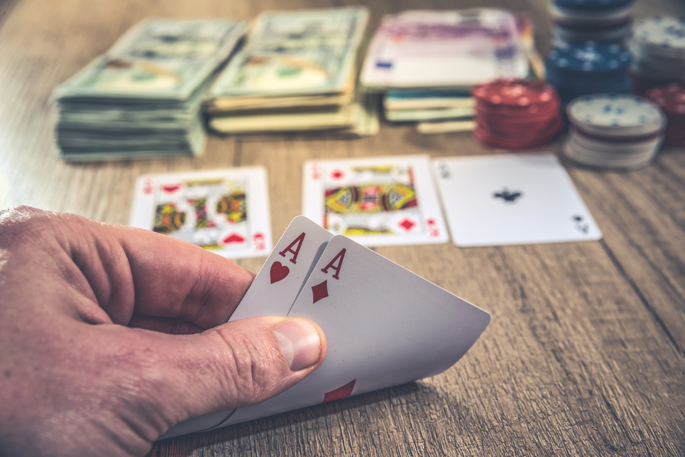 Poker player peeking at hole cards with stacks of cash and chips on table