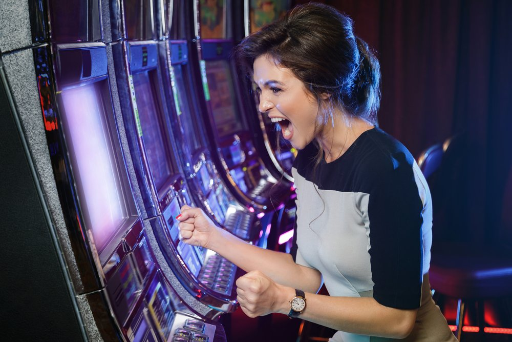 woman expresses happiness and excitement while playing at a slot machine