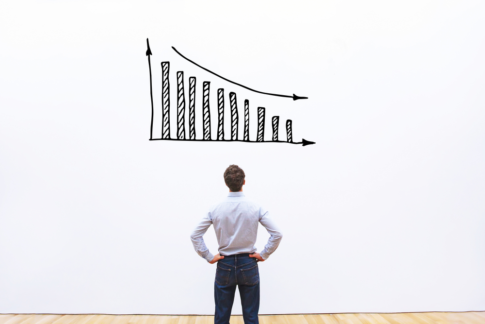 man observing graph showing downtrend and loss
