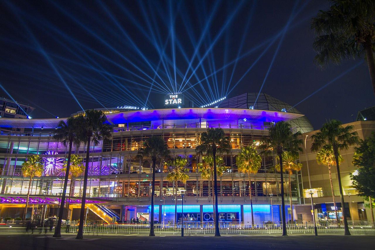 Night shot of the illuminated facade of The Star casino in Sydney, Australia