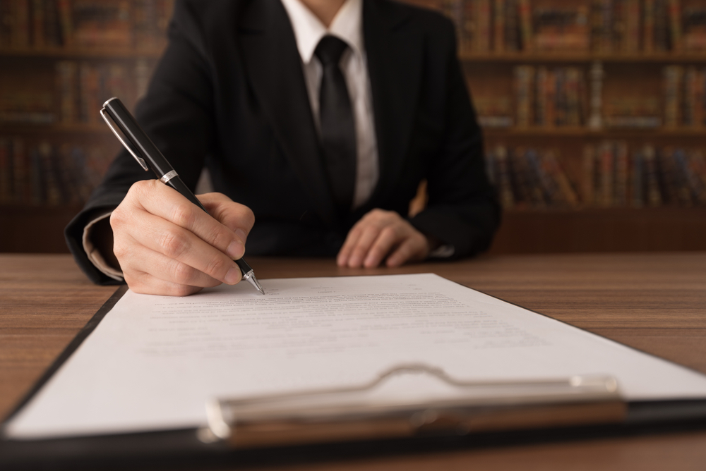 person in suit signing a formal document