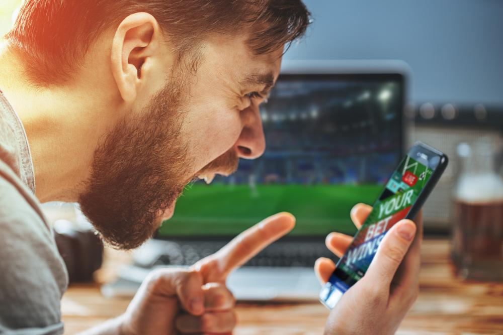 man celebrates as his mobile sports bet wins