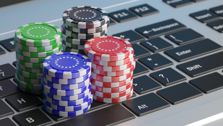 stacks of euro poker chips on laptop keyboard