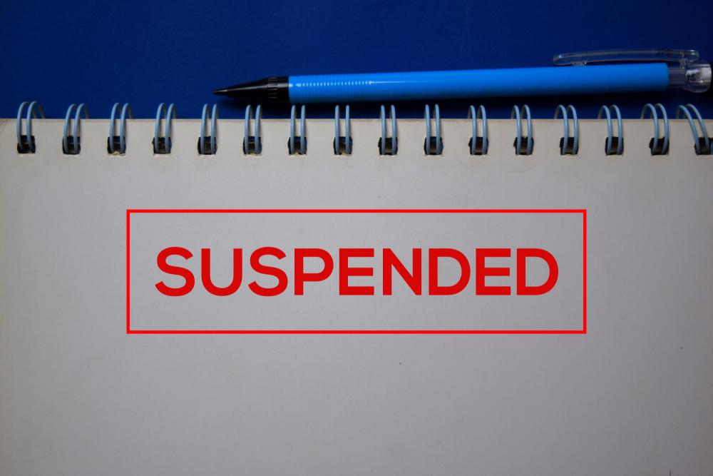 red stamp on notepad reads suspended