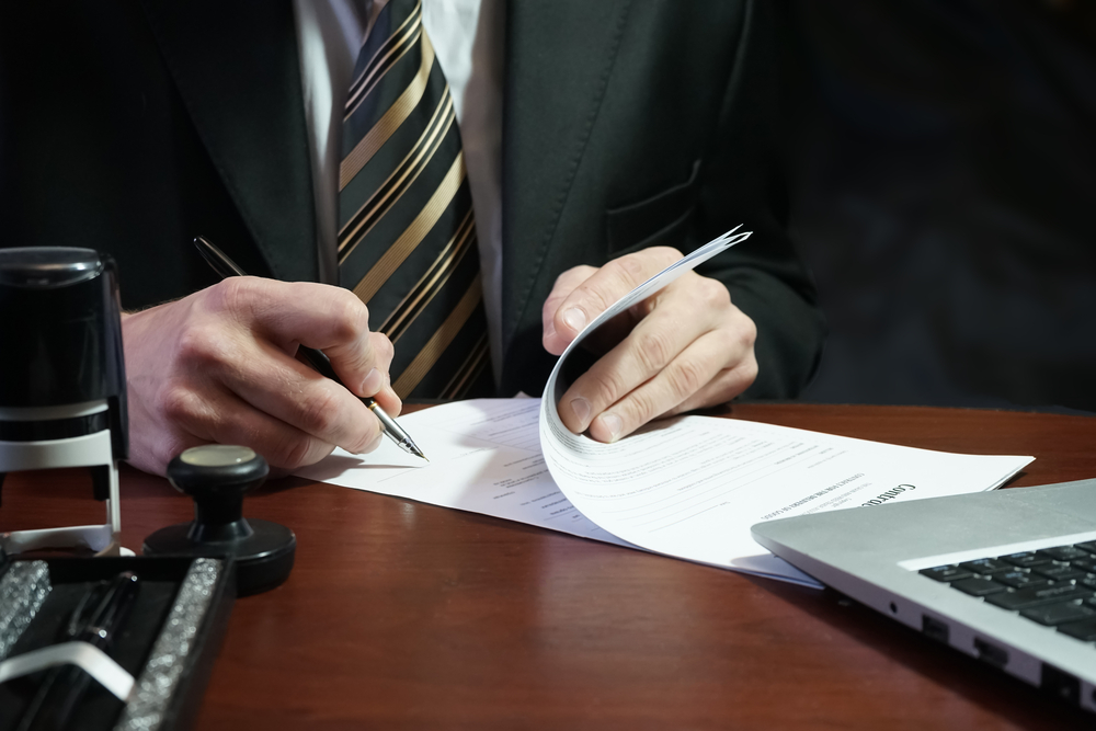businessperson in suit signing a document at a desk