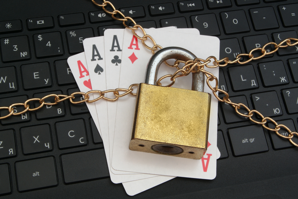 Aces cards placed on computer keyboard and bound by chains and padlock