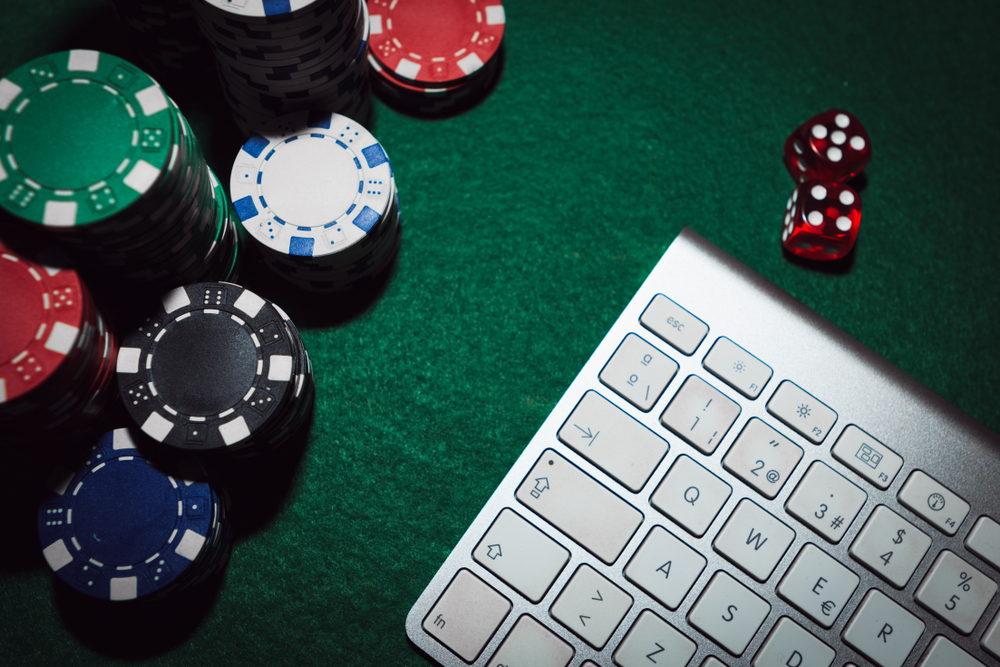 poker chips and computer keyboard on green felt