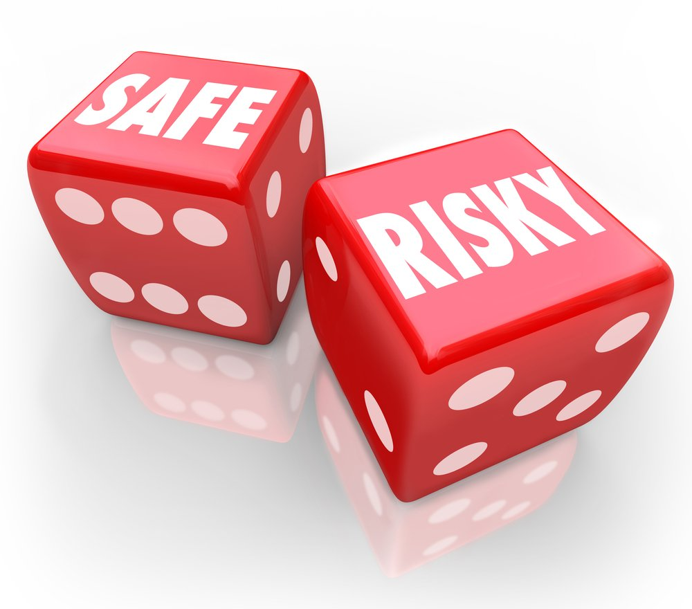 red gambling dice with the words safe and risky printed on one face
