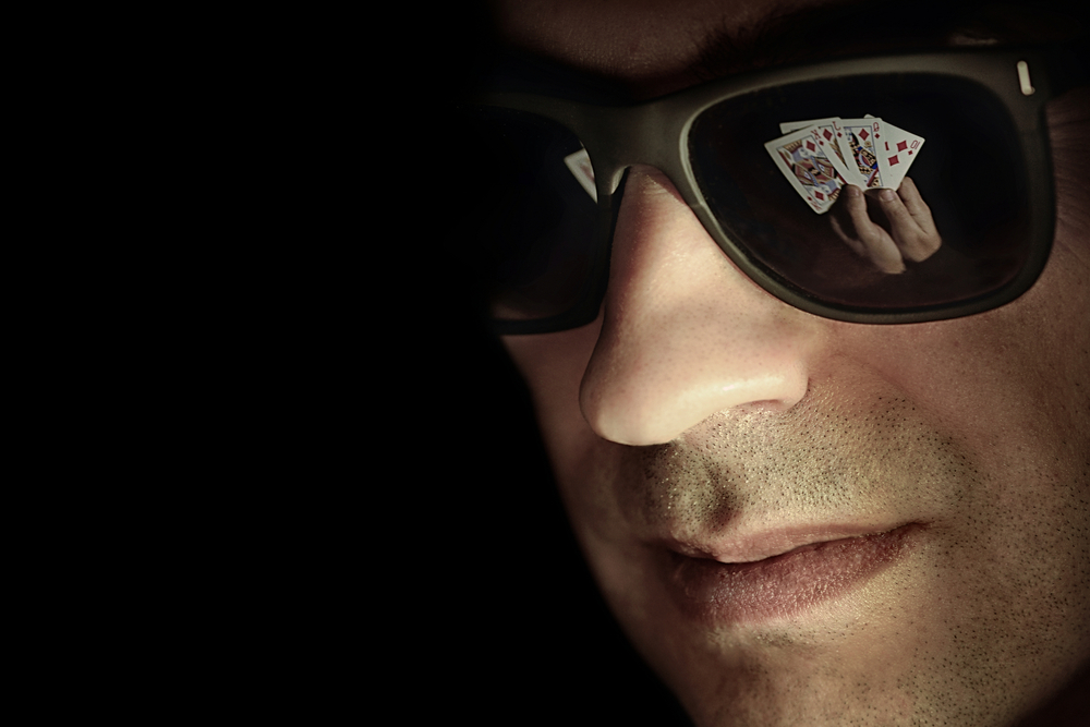 poker cards reflected in male poker player's dark shades