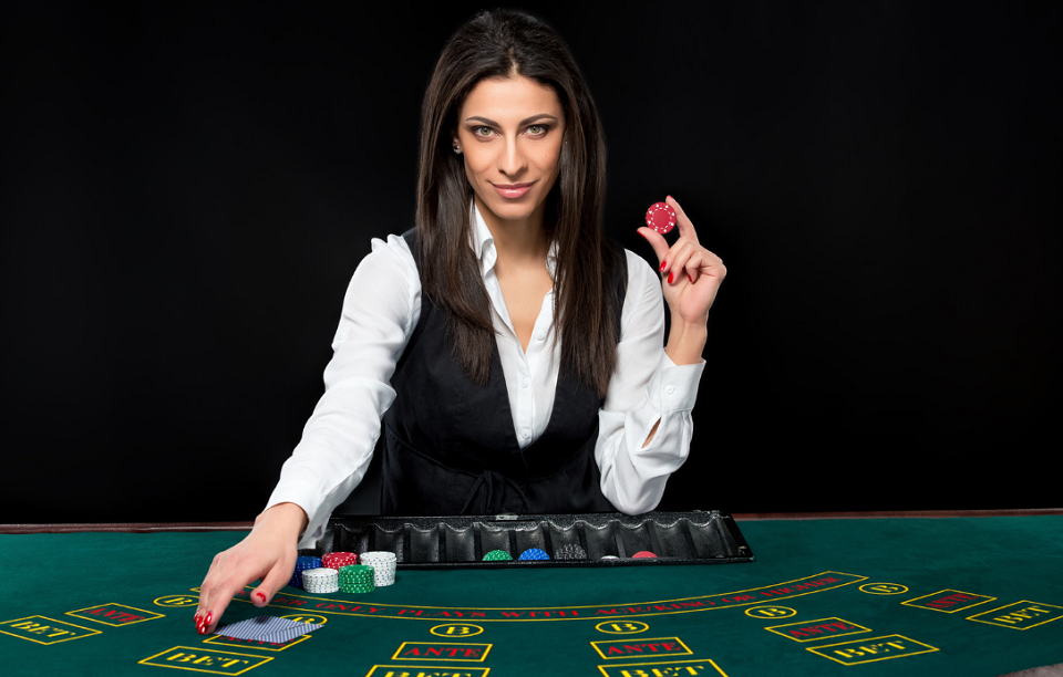 female dealer holding casino chip behind table