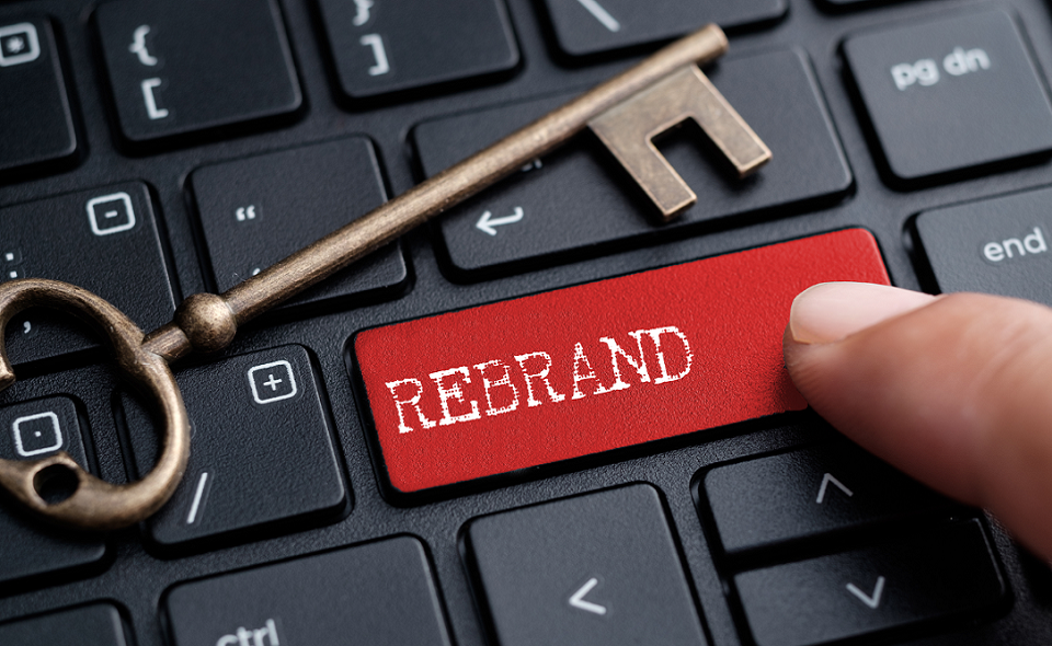 """finger on keyboard with word """"REBRAND"""""""