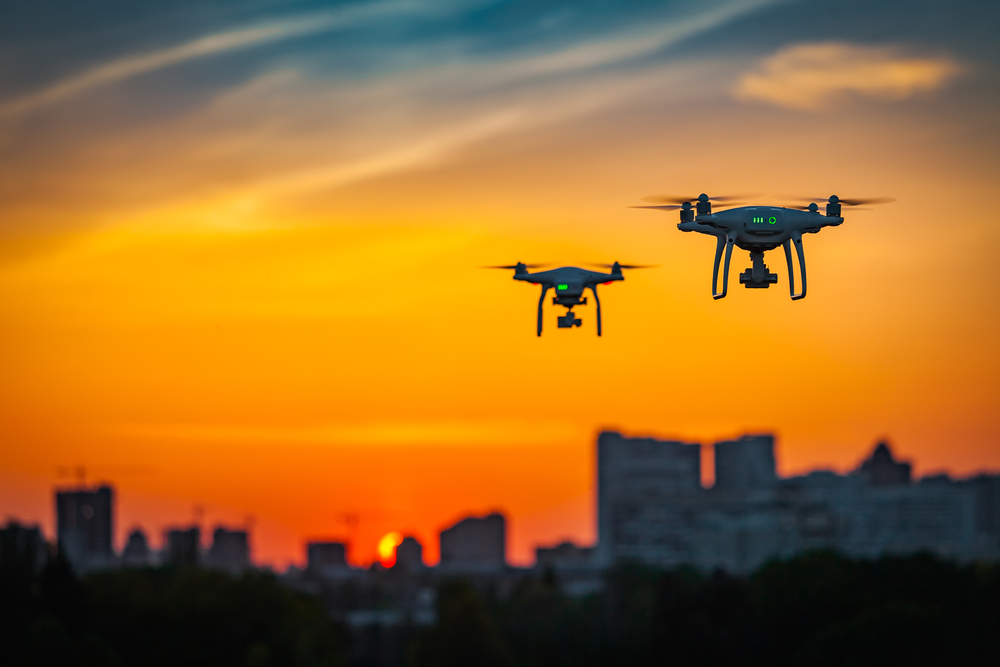 two drones flying against a burnt-orange sunset skyline