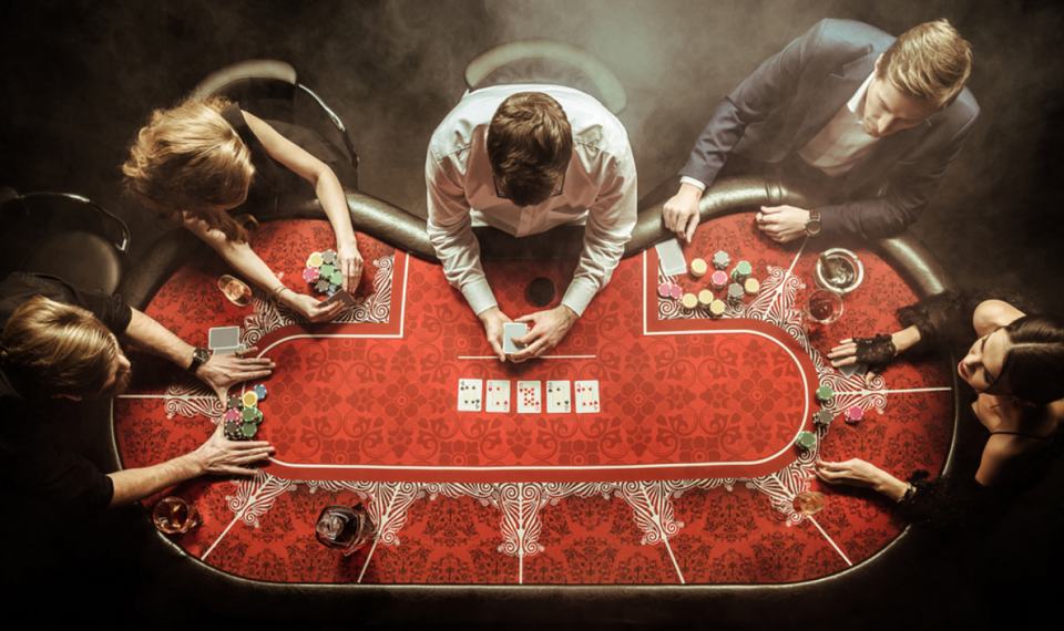 top view of men and women playing poker in casino